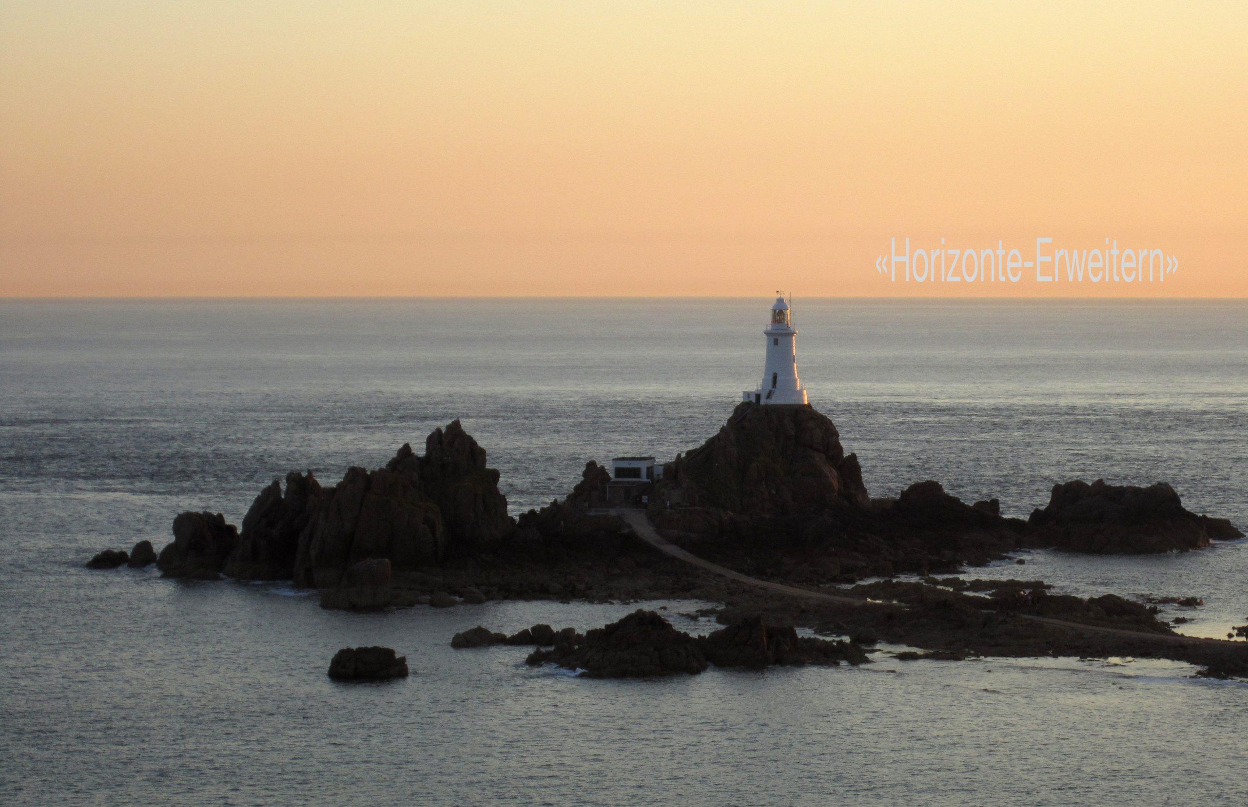 """Der weisse Leuchtturm """"La Corbière"""" an der Südwestküste Jerseys im Abendlicht."""