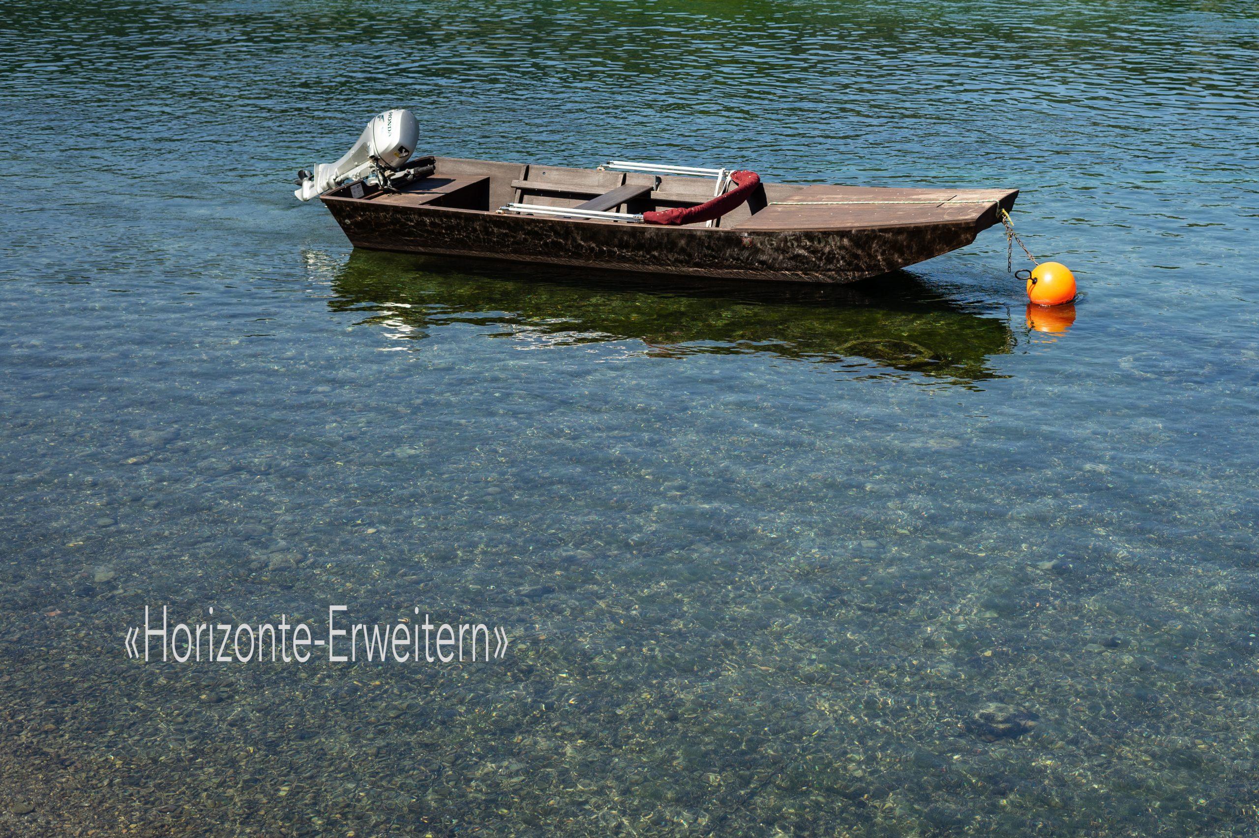 Kleines Holzboot mit hochgezogenem Aussenborder vertäut auf dem Rhein