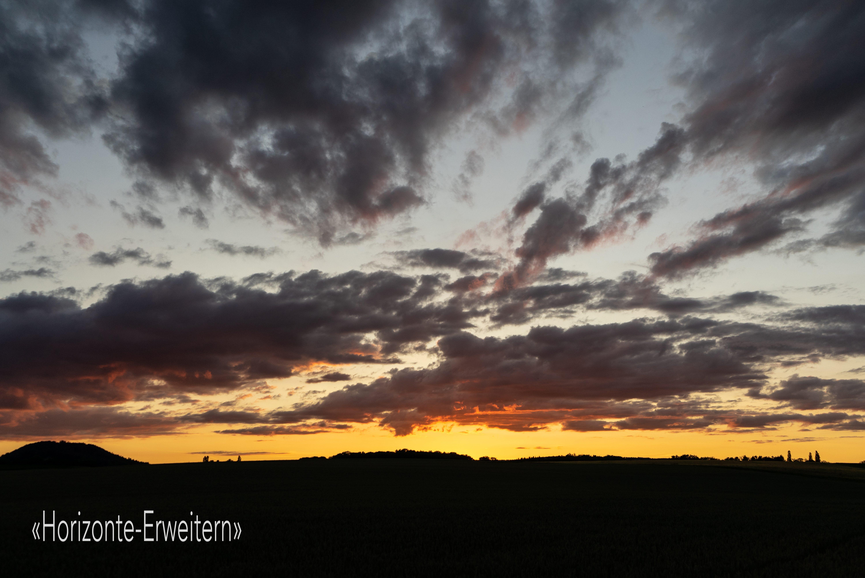 Sonnenuntergang mit von der Sonne angestrahlten dunklen Abendwolken